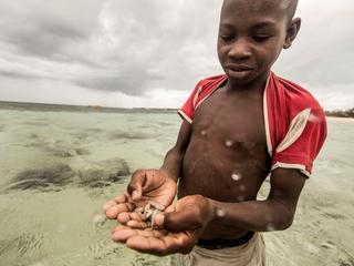 A Nuarro boy shows off his method for catching fish