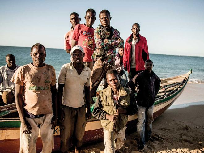 Dino Francisco (center), a fish- ing captain from Praia Nova, with his boat and the majority of his 12-man crew.