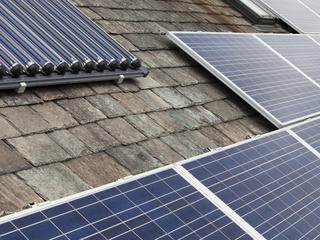 Solar voltaic electricity generating panels and solar hot water panels on a house roof in Ambleside, Cumbria, UK.