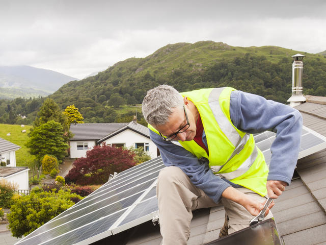 A workman fitting solar thermal panels for heating water, to a house roof in Ambleside, Cumbria, UK, that already has solar PV for generating electricity.
