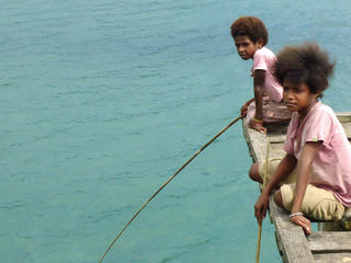 Boys on a dock in Bird's Head Seascape, West Papua, Indonesia