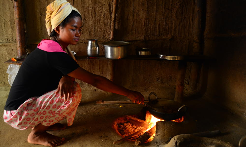 A Nepali woman cooks over her firewood stove. The use of open fires in homes can cause respiratory illness, and contribute to deforestation.
