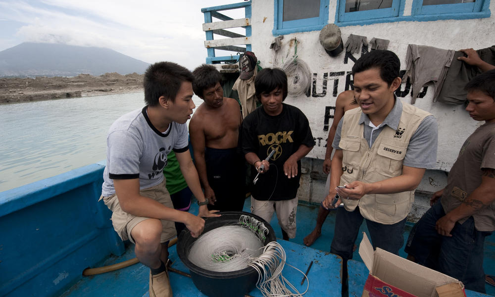 Demonstrating a bycatch de-hooker to longline tuna fishing boat crew