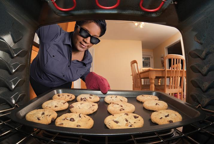 Woman in sunglasses pulling cookies out of the oven