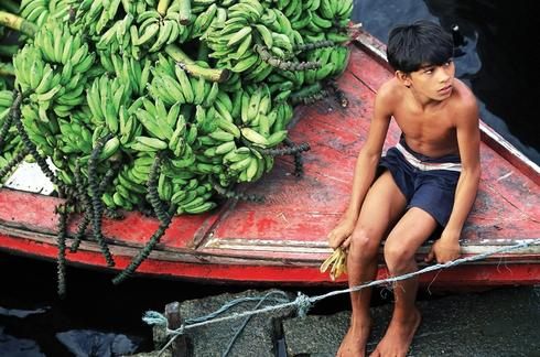 Boy in a boat with bananas