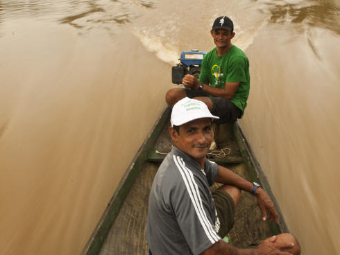 Men boat down river in Amazon