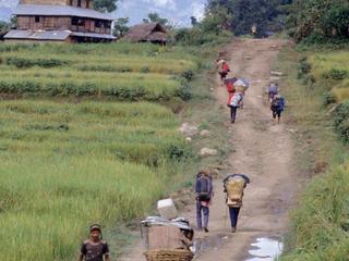 people walk on dirt road in Nepal