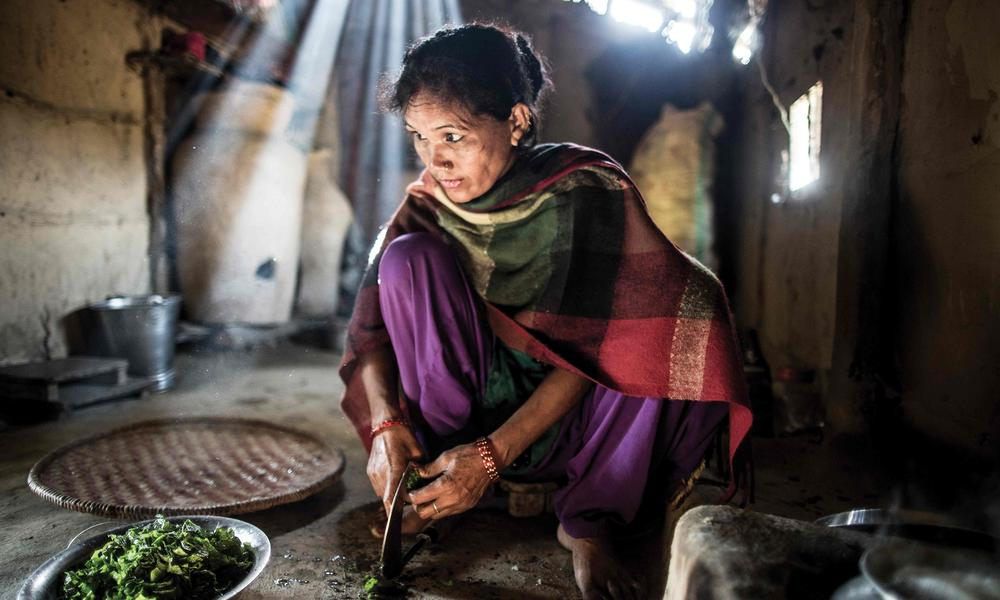 Devi prepares rice, lentils and spinach for her husband and son. The family will eat from this meal for much of the day.