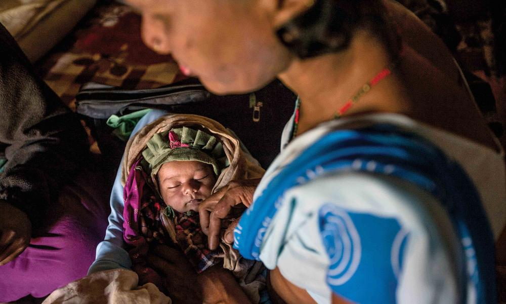 Wearing the blue sari that conveys her training, Devi cradles a baby she delivered a week earlier, checking the infant's temperature, heartbeat and other vital signs.
