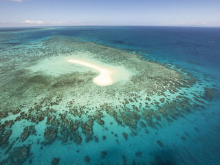 A small island and fringing reef seen from the air. Great Barrier Reef, Australia.