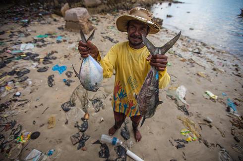 Fisherman holding up his catch at Tun Mustapha Park, Kudat, SABAH
