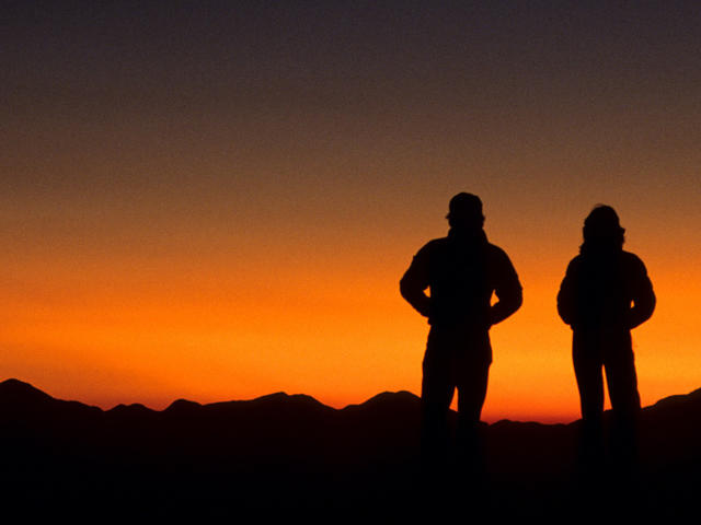 Two hikers silhouetted at sunset, Austrian camp, Dhampus. Annapurna Area, Nepal.