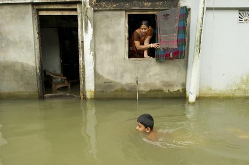 Child swimming near a flooded building