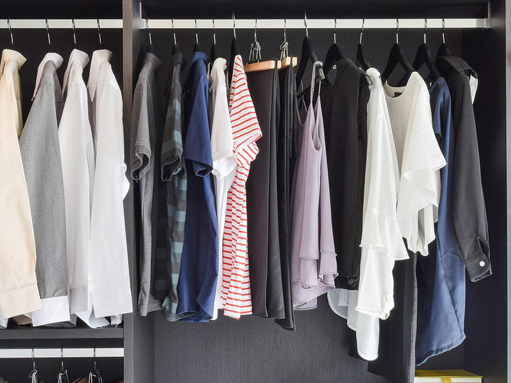modern closet with row of cloths hanging